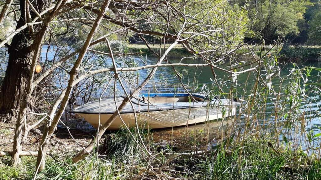 Een bootje ligt in de rivier Krupa.