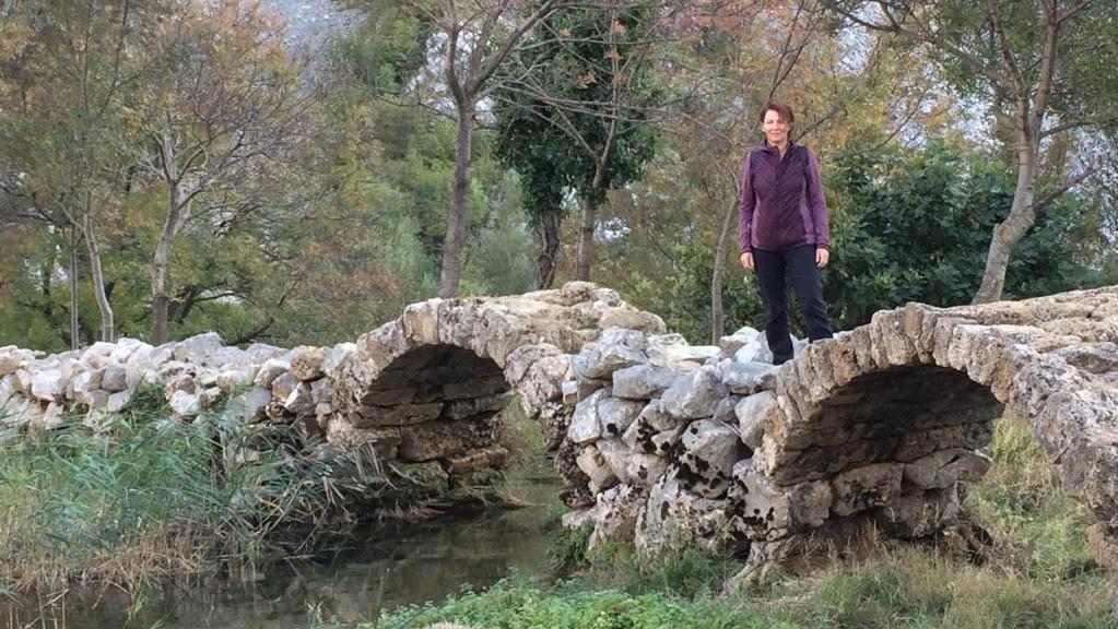 Wandelvrouw staat op de brug van Kude over de rivier van Krupa