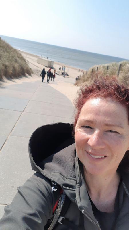 Wandelvrouw bij strandopgang Zee van Tijd Julianadorp
